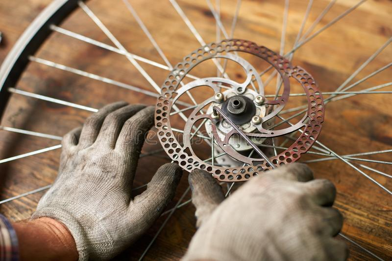 Male mechanic working in bicycle repair shop using tools. Cropped shot of mechanic working in bicycle repair shop, repairer fixing bike wheel using special tool royalty free stock photos