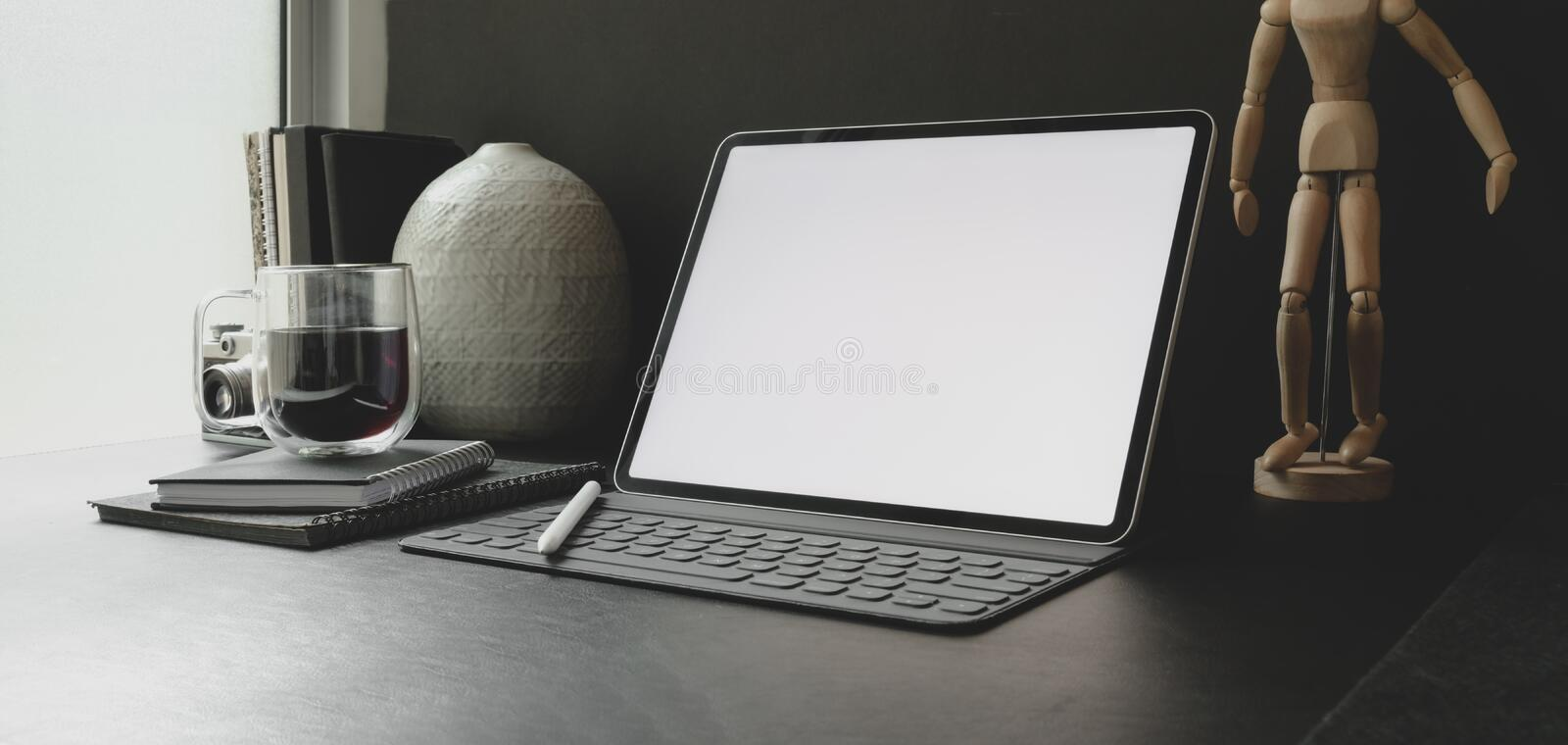 Cropped shot of modern workplace with blank screen tablet with office supplies with black wall. Background royalty free stock photo