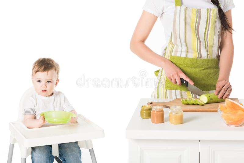 Cropped shot of mother in apron cutting zucchini and son sitting in highchair with plate royalty free stock image