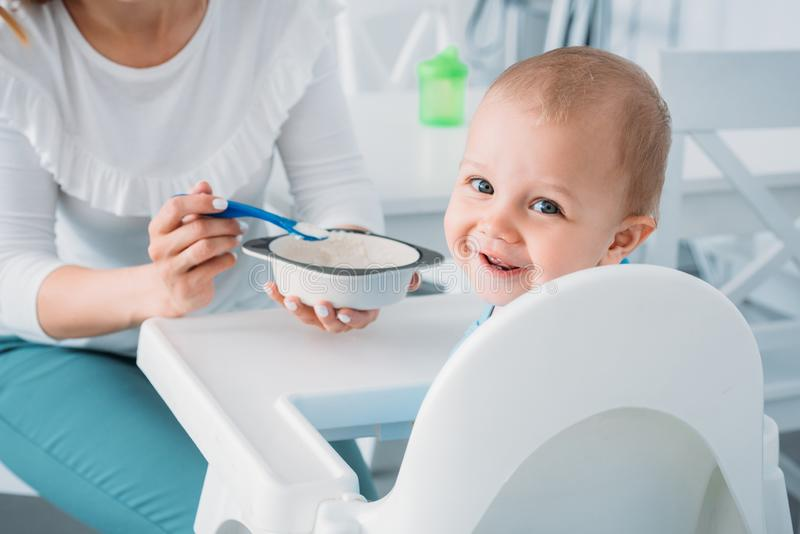 Cropped shot of mother feeding happy child. With porridge while he looking at camera stock images