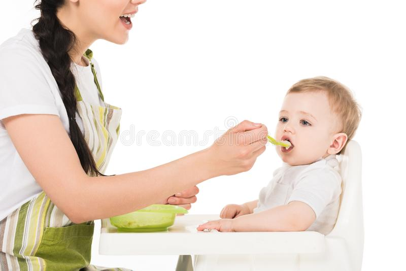 Cropped shot of mother feeding little son sitting in highchair. Isolated on white background stock photo