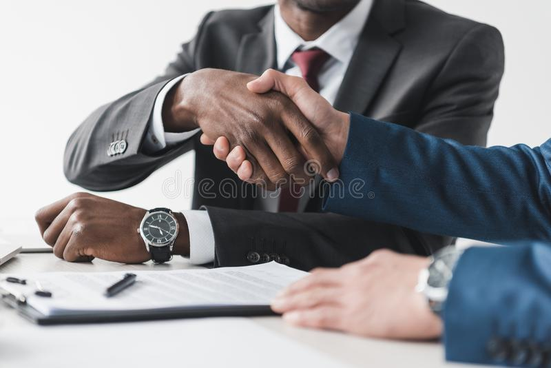 Cropped shot of multicultural businessmen shaking hands during contract signing. At workplace royalty free stock photography