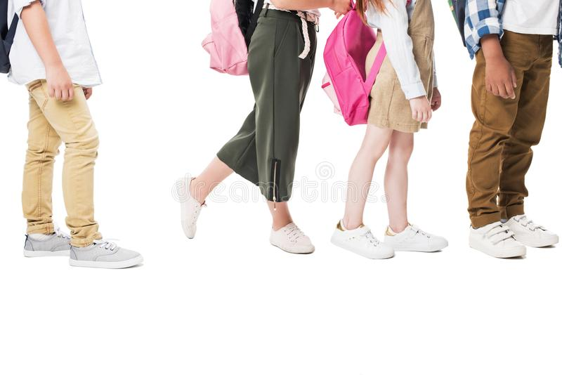 cropped shot of multiethnic children with backpacks standing together isolated on white stock photography