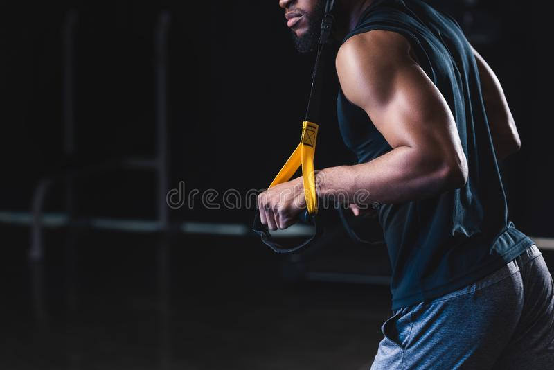 Cropped shot of muscular african american man. Exercising with resistance bands royalty free stock photo