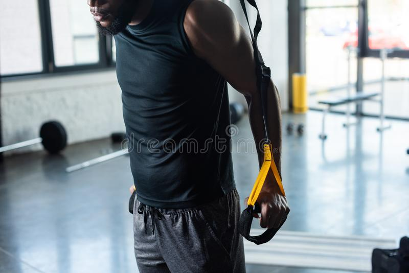 Cropped shot of muscular young african american man. Training with fitness straps in gym royalty free stock image