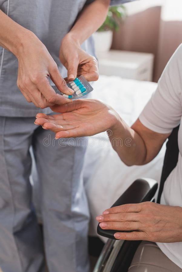 cropped shot of nurse giving pills to senior patient royalty free stock image