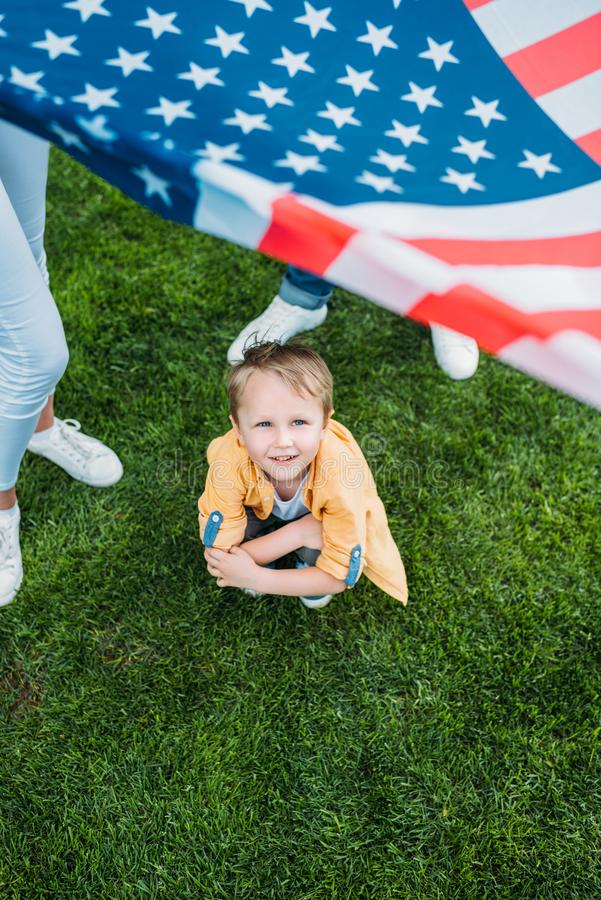 Cropped shot of parents holding american flag and little son crouching. On grass royalty free stock image