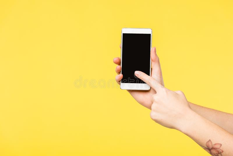 Cropped shot of person holding smartphone with black screen isolated. On yellow stock photo