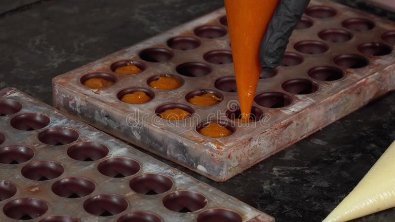 Chocolatier preparing handmade cream filled chocolate candy. Cropped shot of a professional chocolatier squeezing fruit cream into chocolate mold. Confectioner royalty free stock images