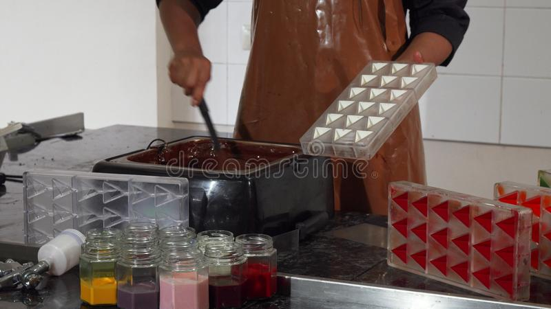 Professional chocolatier working at the kitchen. Cropped shot of a professional chocolatier wearing cooking uniform and apron working with hot melting chocolate stock image