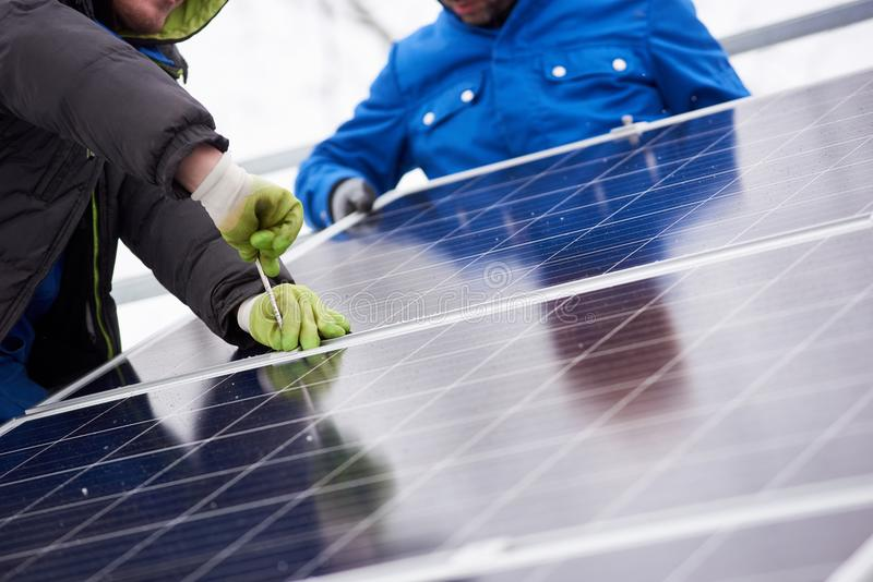 Professional electrician worker installing solar panels. Cropped shot of professional electricians working on solar power plant factory renewable energy royalty free stock images