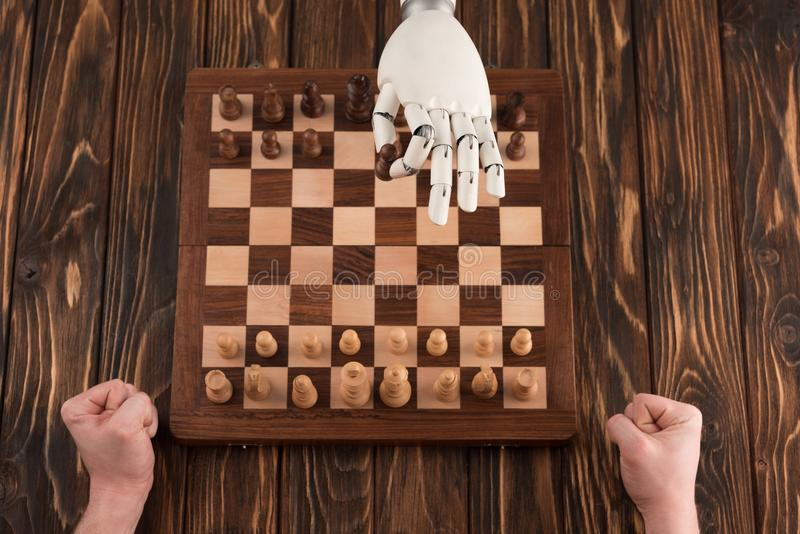 cropped shot of robot playing chess with human on wooden surface stock photo
