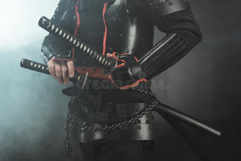 Cropped shot of samurai in armor with swords on dark background. With smoke royalty free stock photo