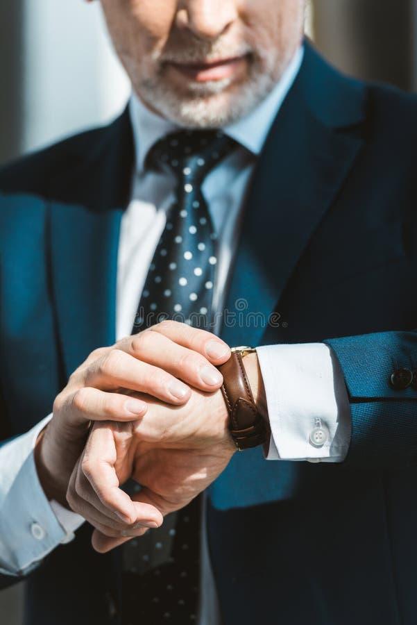 Cropped shot of senior businessman. In formal wear checking wristwatch stock photo