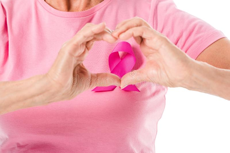 cropped shot of senior woman in pink t-shirt with breast cancer awareness ribbon showing hand heart symbol royalty free stock photos