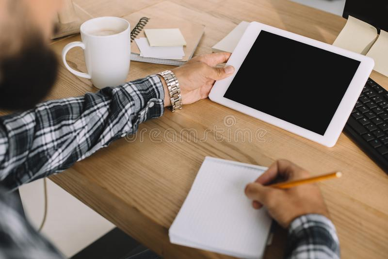 cropped shot of seo using tablet with blank screen and writing notes royalty free stock image
