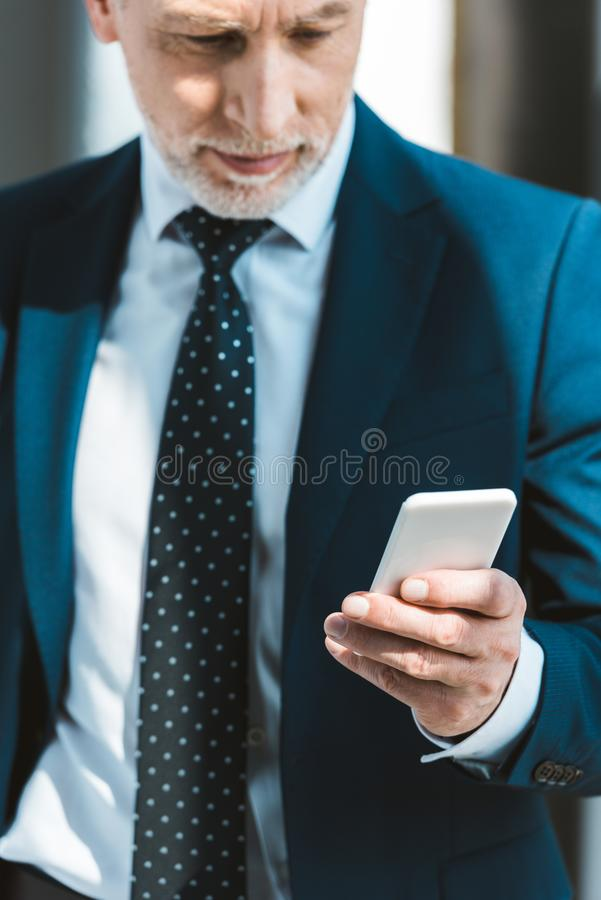 Cropped shot of serious senior businessman. Using smartphone royalty free stock images