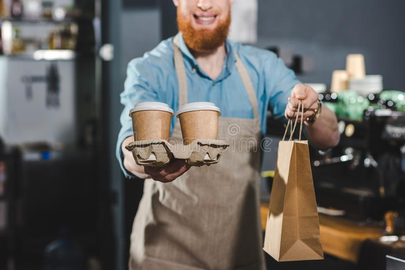 cropped shot of smiling bearded barista holding disposable coffee cups and paper bag stock image