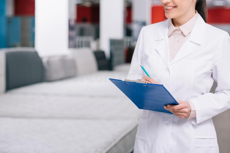 cropped shot of smiling shop assistant in white coat with notepad in furniture shop stock photo