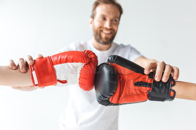 cropped shot of smiling trainer holding hands of boys in boxing gloves stock photo