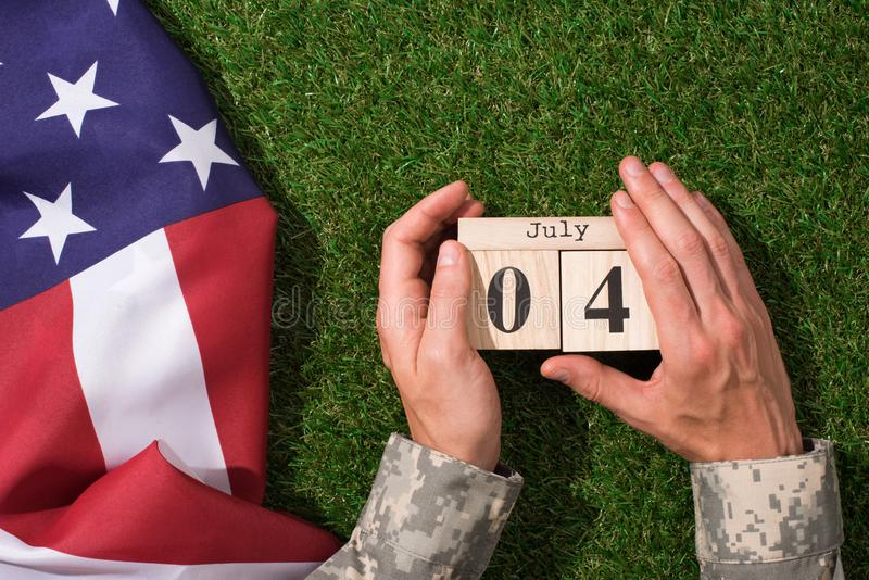 Cropped shot of soldier in military uniform holding calendar with 4th july date with american flag on green grass, americas. Independence day concept stock photography