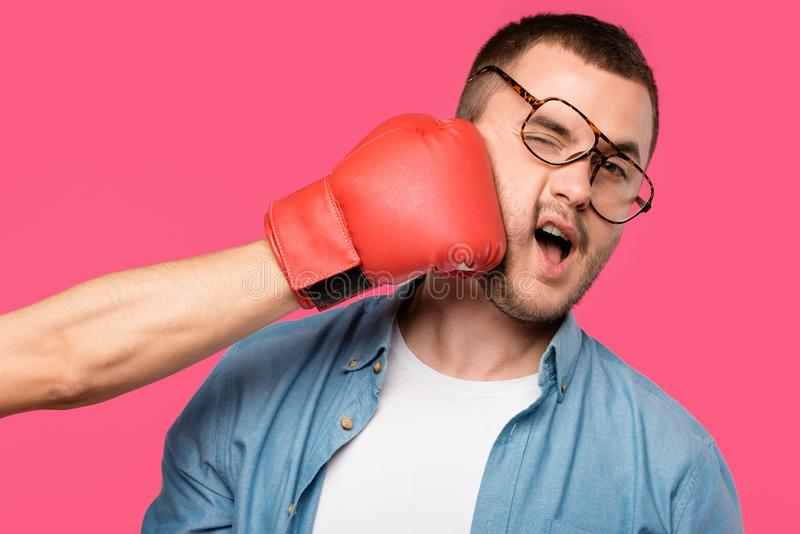 Cropped shot of someone in boxing glove hitting man in eyeglasses isolated. On pink stock image
