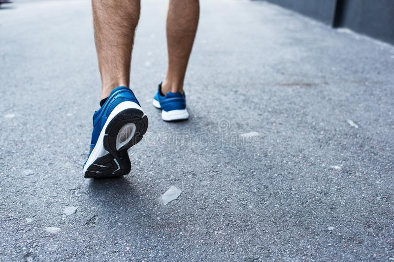 Cropped shot of sportsman in jogging sneakers royalty free stock photography