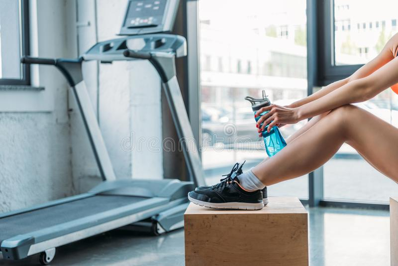 cropped shot of sportswoman sitting on wooden box with bottle of water in front of treadmill royalty free stock image