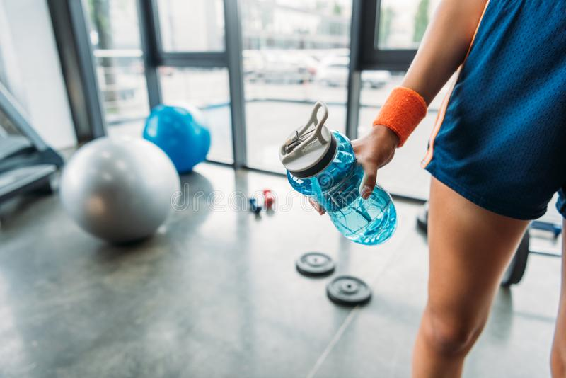 cropped shot of sportswoman in wristband holding bottle of water royalty free stock image