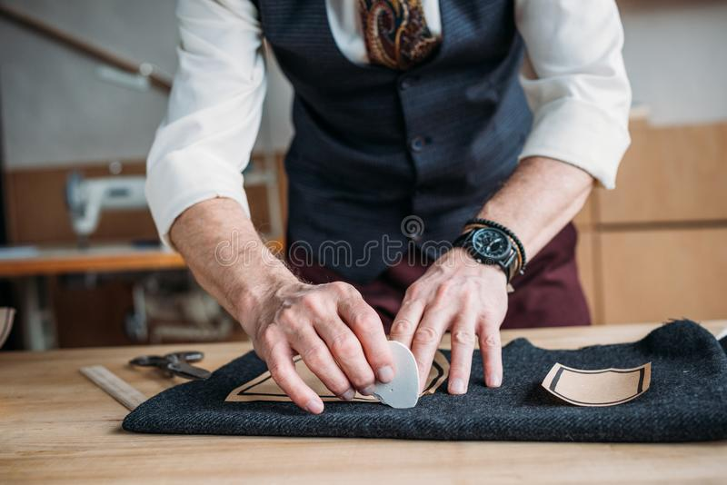 Cropped shot of stylish tailor marking cloth pattern with chalk. At sewing workshop stock photography