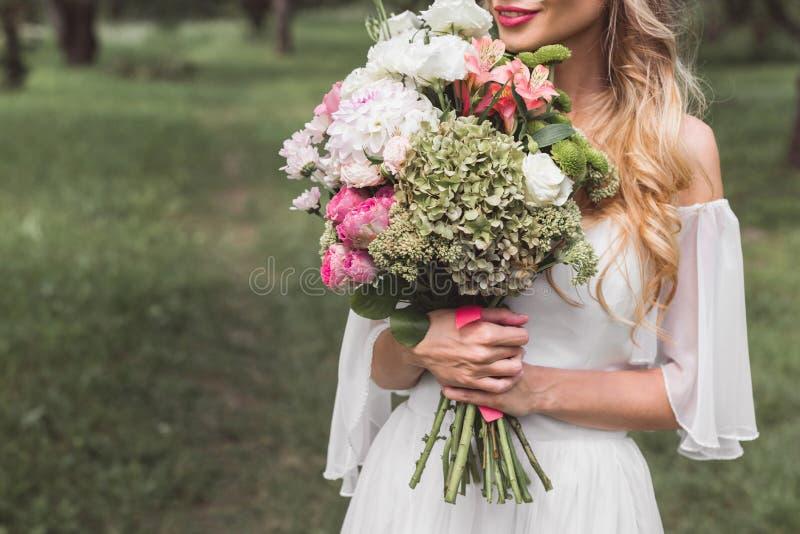 cropped shot of tender smiling blonde bride holding wedding royalty free stock photo