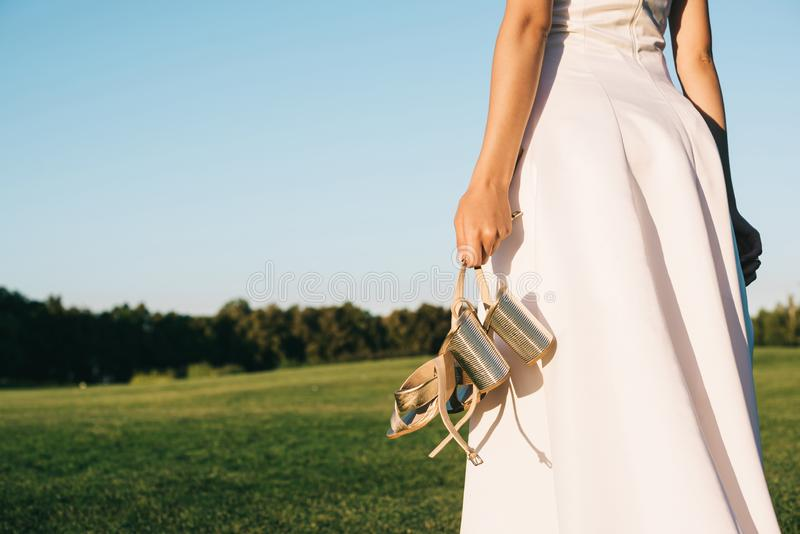 Cropped shot of tender young bride in wedding dress holding shoes and walking. In park royalty free stock images