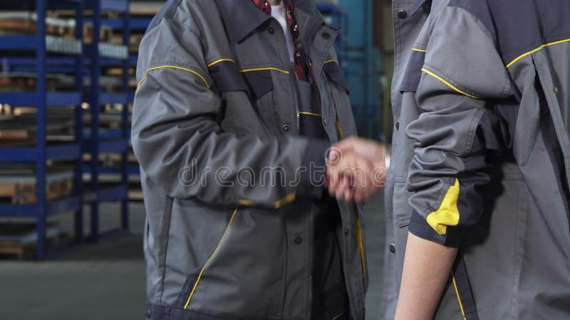 Cropped shot of two female workers shaking hands at the factory storage royalty free stock image