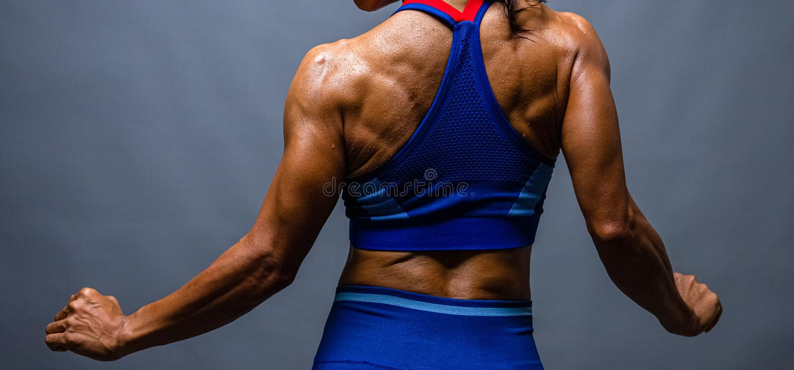 Cropped shot of a unrecognizable strong bald bodybuilder with six pack. Bodybuilder woman with perfect abs, shoulders,biceps,. Triceps and chest, personal royalty free stock photo
