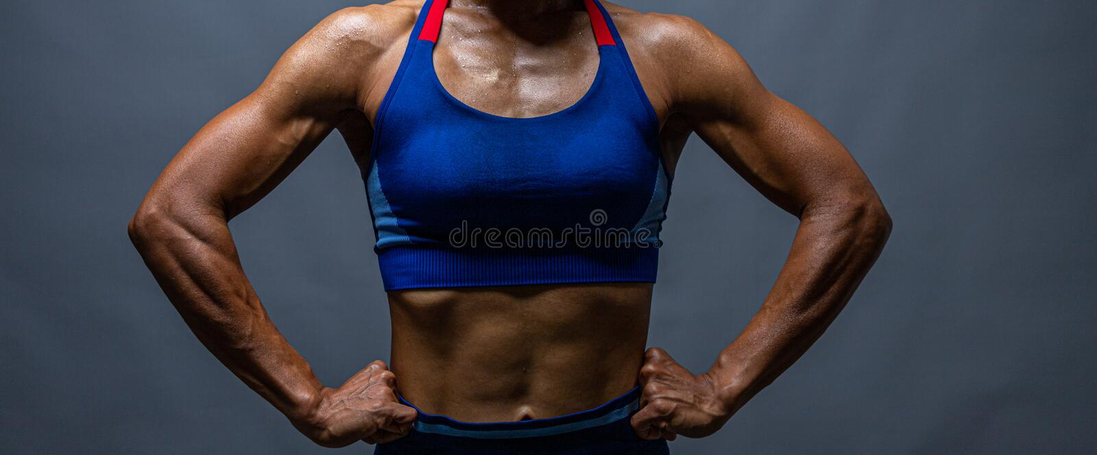Cropped shot of a unrecognizable strong bald bodybuilder with six pack. Bodybuilder woman with perfect abs, shoulders,biceps,. Triceps and chest, personal stock photography