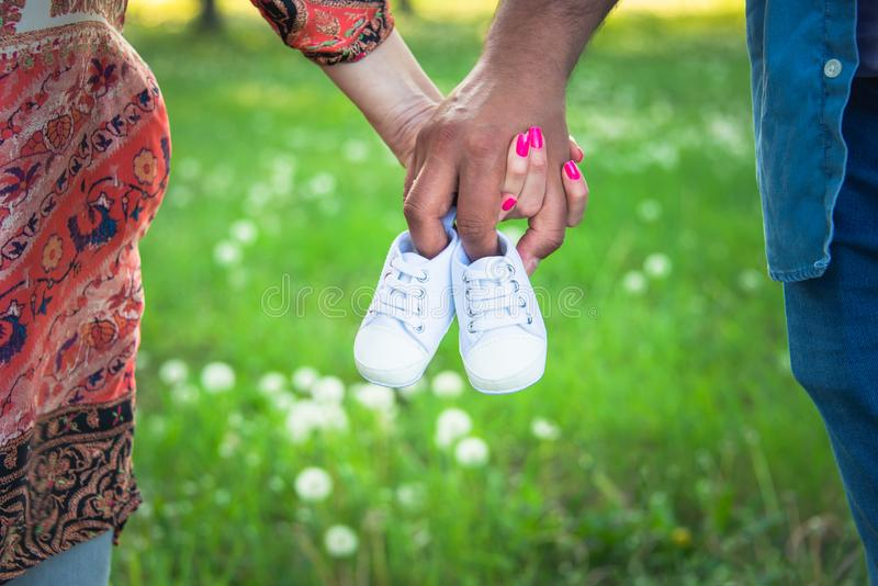 Cropped shot view of expecting parents holding baby shoes. Pregnancy, maternity and new family concept. stock images