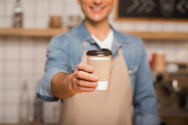 Waiter holding coffee to go. Cropped shot of waiter holding coffee to go in paper cup with blurred background royalty free stock photo