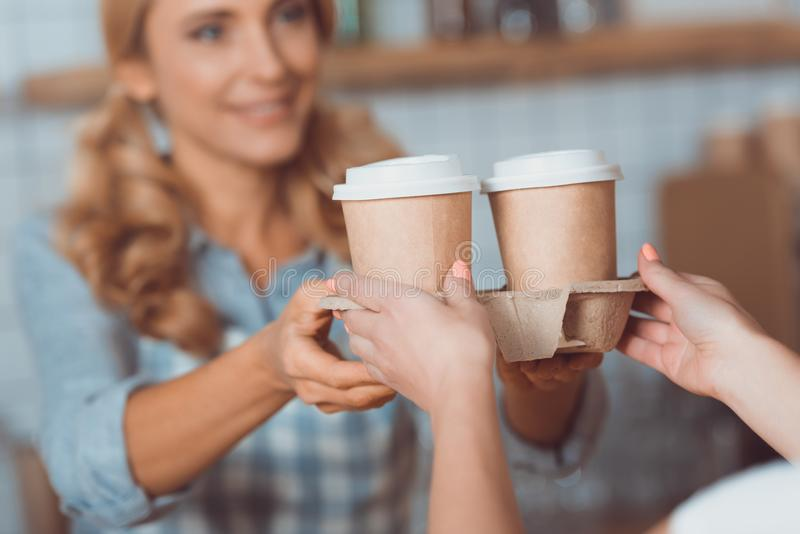 Cropped shot of waitress and buyer holding coffee to go in paper. Cups royalty free stock photography