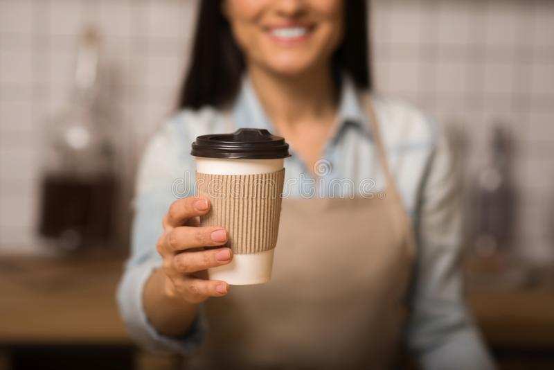 Waitress holding coffee to go. Cropped shot of waitress holding coffee to go in paper cup with blurred background stock photography