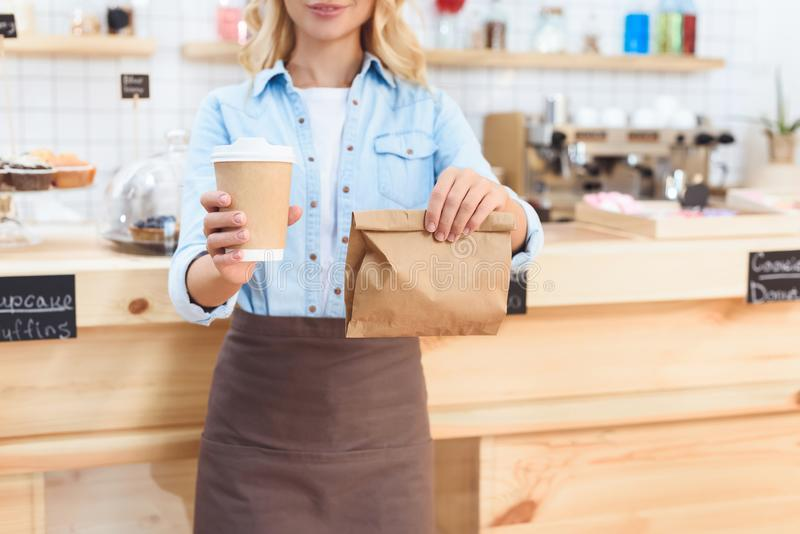 Cropped shot of waitress holding coffee to go in paper cup and take away food. In paper bag stock images