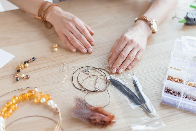 Cropped shot of woman with beads and threads for handmade accessories. In workshop stock image