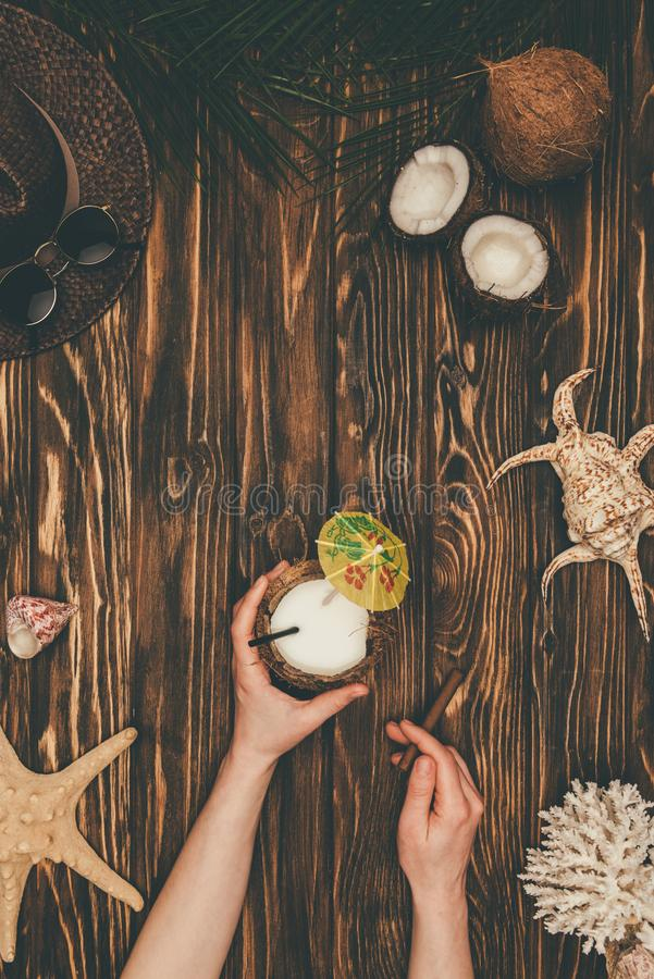 Cropped shot of woman with coconut cocktail and cigar on wooden surface surrounded with various tropical. Travel attributes royalty free stock photos