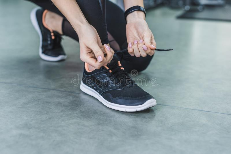 cropped shot of woman lacing up sneakers stock photo