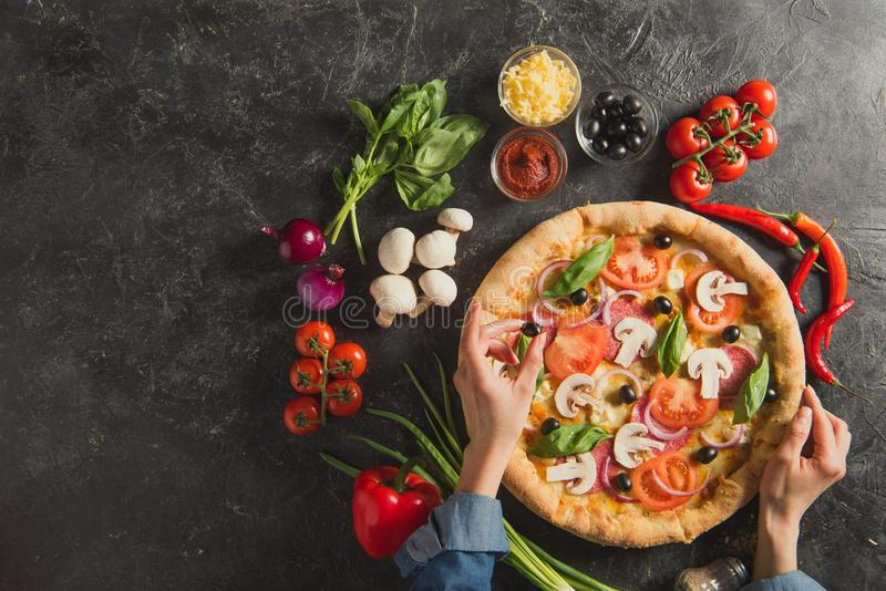 Cropped shot of woman putting black olives on italian pizza. On dark tabletop royalty free stock photos