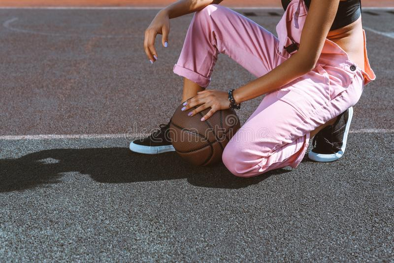 Cropped shot of woman in sports bra and pink overalls sitting at ground of sports field. With basketball ball royalty free stock images