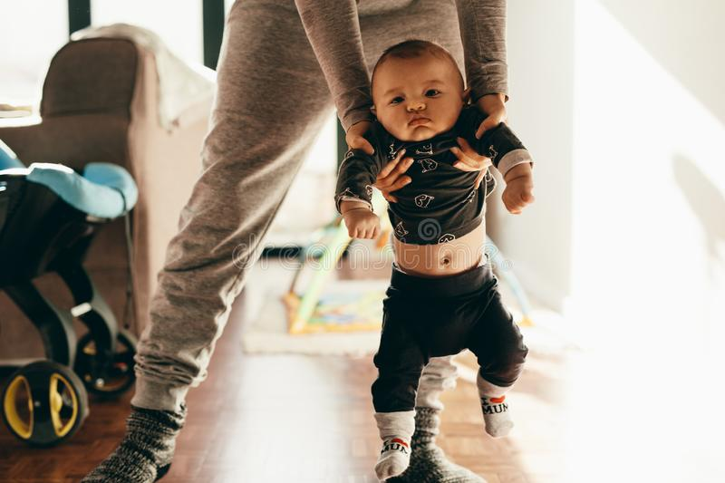 Mother making her baby walk stock images