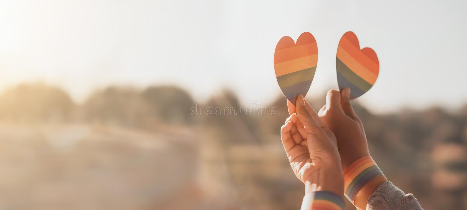 Cropped shot of women LGBT lesbian couple hands holding a heart shape painted like a rainbow pride. LGBT equal rights concept royalty free stock photography
