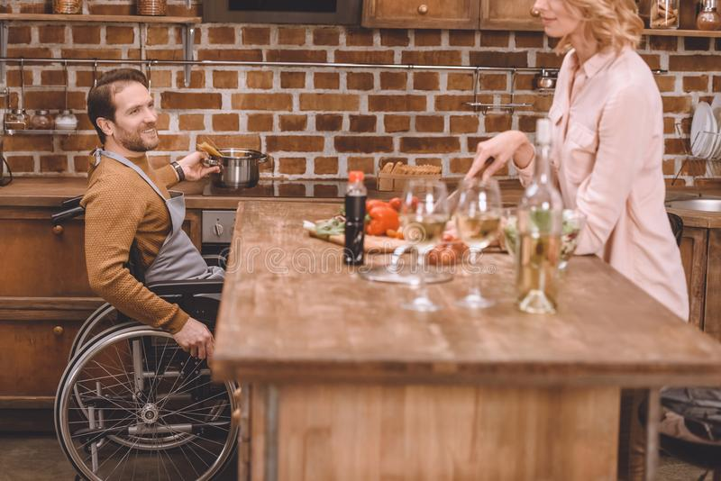 cropped shot of woman with man in wheelchair cooking dinner together stock photo