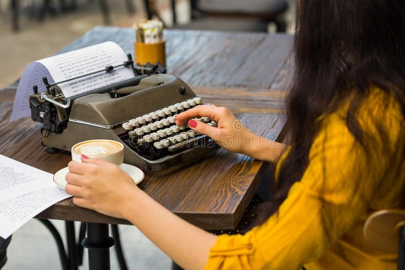 Cropped shot of a writer`s hands typing on retro typewriter stock photo