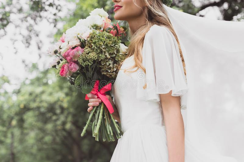 cropped shot of young bride in wedding dress and veil holding beautiful bouquet stock photo